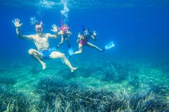 La familia se zambulle en el mar en máscaras Imagen de archivo