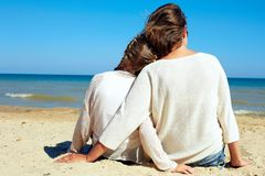 La familia sienta el abrazo en el mar y mira el agua Tiempo imagen de archivo