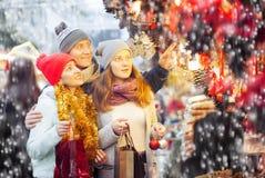 La familia sonriente elige la decoración de la Navidad Imagen de archivo libre de regalías
