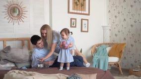 La familia sonriente en la cama, donde el papá da a pequeña hija un juguete, y la mamá coge el teléfono almacen de video
