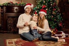 La familia sonriente feliz cerca del árbol de navidad celebra Año Nuevo Imagen de archivo libre de regalías