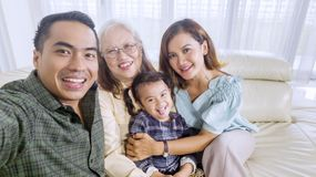 La familia sonriente toma una imagen del grupo en casa fotografía de archivo libre de regalías