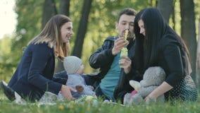 La familia sueca con el pequeño soplo del hijo burbujea en una sobrecama en parque almacen de video