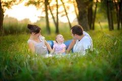 La familia tiene un resto en el parque fotografía de archivo libre de regalías
