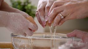 La familia todo juntos rompe los huevos en una placa para las manos de la prueba de los padres y del hijo durante cocinar la past metrajes