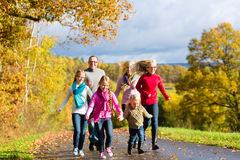 La familia toma un paseo en bosque del otoño Foto de archivo libre de regalías