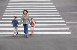 La familia va a cruzar el camino foto de archivo