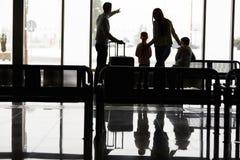 La familia y los niños están esperando en el terminal de aeropuerto imagenes de archivo