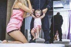 La famille à la maison dans la maman de chambre à coucher, le papa et le bébé sont togeth heureux Photos stock