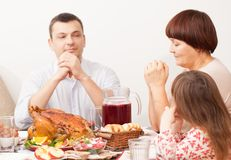 La famille à la table pour un repas de la Turquie cuite au four Photos libres de droits