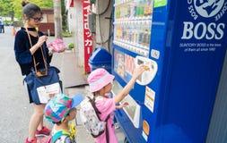 La famille achètent des boîtes de boisson non alcoolisée des vendeurs de pièce de monnaie Photo libre de droits