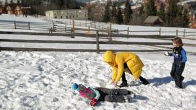 La famille active apprécie Sunny Warm Weather During Vacation dans la campagne La mère agitée joue dans Snowball banque de vidéos