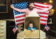 La famille américaine moderne avec le drapeau des Etats-Unis et le papier montent en flèche Photo stock