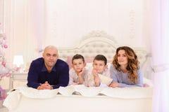 La famille amicale cause le mensonge sur le lit, la maman et le papa avec leur enfant Image libre de droits