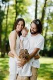 La famille amicale habillée dans les vêtements blancs prend le repos en parc Le papa et la maman étreignent leurs enfants photographie stock libre de droits