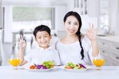 Le garçon et la maman sont heureux avec de la salade Image stock