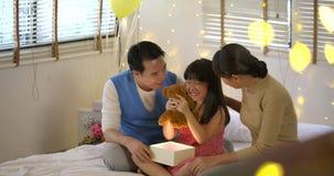La famille asiatique heureuse célébrant des cadeaux d'ouverture d'anniversaire du ` s de fille et se réjouissent sur le lit banque de vidéos