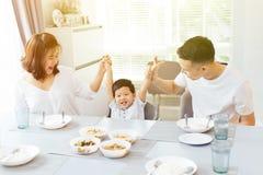 La famille asiatique heureuse soulevant le ` s d'enfant remet et souriant tout en ayant un repas ensemble image libre de droits