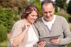 La famille assez mûre utilise un ordinateur portable pour l'amusement Images stock