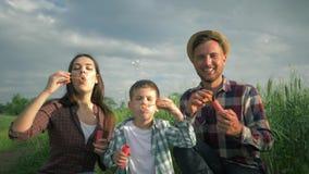 La famille attirante jouant avec des bulles de savon, l'enfant de sourire avec la m?re et le p?re dans des chemises ? carreaux on banque de vidéos