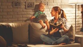 La famille avant mère allante au lit lit à son nea de livre de fils de bébé photographie stock libre de droits