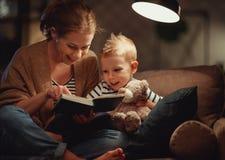 La famille avant m?re allante au lit lit ? son livre de fils d'enfant pr?s d'une lampe dans la soir?e photo libre de droits