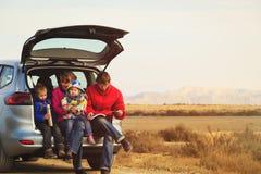 La famille avec deux enfants voyagent en voiture en montagnes Image stock