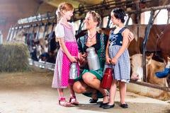 La famille avec du lait peut à la ferme de vache Photographie stock libre de droits