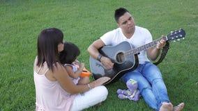 La famille avec l'enfant marche sur l'herbe verte banque de vidéos