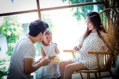 La famille avec la petite fille dans les joueurs peut téléphoner Photographie stock libre de droits