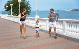 La famille avec le fils de trois ans court par la mer Photo libre de droits