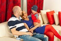 La famille avec le gosse s'asseyent sur le divan Photo stock