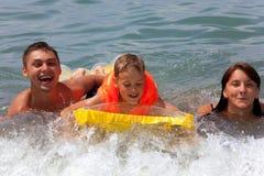 La famille avec le matelas jaune se baigne en mer photo stock