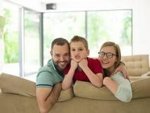 La famille avec le petit garçon apprécie dans le salon moderne photos libres de droits