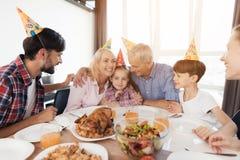 La famille célèbre l'anniversaire d'une petite fille Les grands-parents s'asseyent l'un à côté de l'autre et étreignent la fille Photographie stock