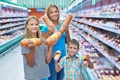 La famille choisit des saucisses dans la boutique Photo stock