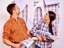 La famille colle le papier peint à la maison photo stock
