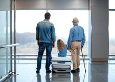 La famille curieuse apprécie la vue au hall terminal Photo stock