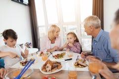 La famille dîne à la table de fête pour le thanksgiving La grand-mère alimente sa petite petite-fille Photo stock