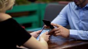 La famille d'affaires a concentré des smartphones la date au restaurant, indifférence image libre de droits