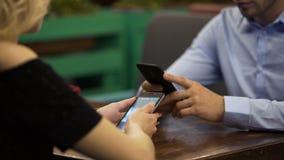 La famille d'affaires s'est concentrée sur des smartphones la date au restaurant, indifférent banque de vidéos