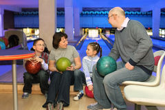 La famille dans le reste et communiquent dans le club de bowling Images stock