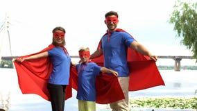 La famille dans le super héros costume la pose pour l'appareil-photo, l'unité et le repos extérieur photographie stock libre de droits