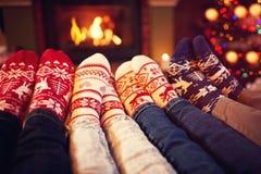 La famille dans les chaussettes s'approchent de la cheminée en hiver Photo libre de droits