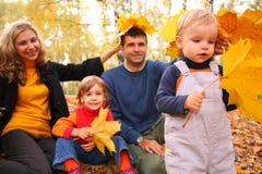 La famille de quatre avec l'érable jaune part en bois image libre de droits