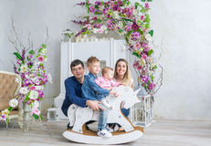 La famille de quatre heureuse se reposent dans la chambre avec des fleurs et jouent avec des enfants sur son cheval en bois de jo Images stock