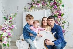 La famille de quatre heureuse se reposent dans la chambre avec des fleurs et jouent avec des enfants sur son cheval en bois de jo Image libre de droits