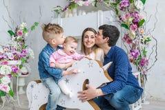 La famille de quatre heureuse se reposent dans la chambre avec des fleurs et jouent avec des enfants sur son cheval en bois de jo Photo stock
