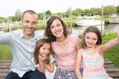La famille de quatre incitent à selfie le père extérieur à enfanter et la soeur de fille photos libres de droits