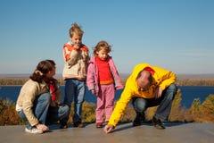 La famille de quatre personnes marche en jour solaire d'automne Photos stock